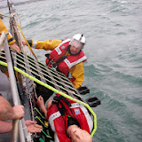 17 July 2011 – ALB crew members pull the Jason's Cradle onboard Poole's Tyne class lifeboat with Crew Member Scott Rowland guiding the casualty.  Photo: RNLI Poole/Anne Millman