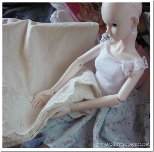 ball jointed doll admiring a lace pillow case