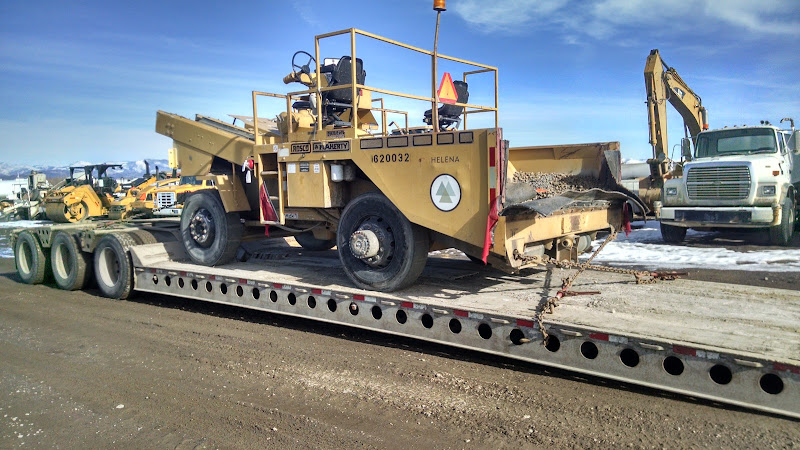 chip spreader being secured and hauled on a flatbed trailer