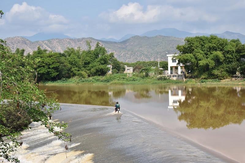 Người dân vẫn chạy xe qua lại xuyên qua dòng nước của đập.