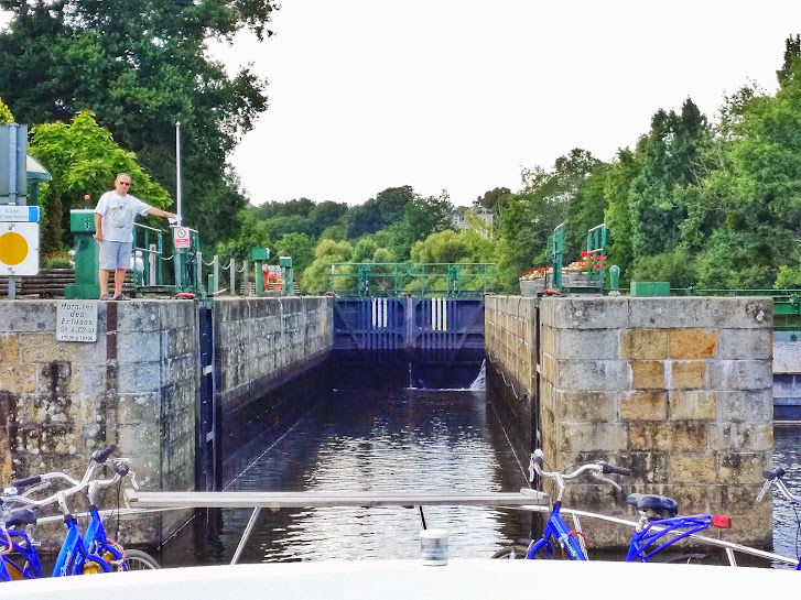 Entering one of the narrow locks with the lock keeper guiding us...in French.