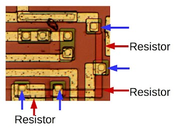 Three resistors (red) on the die of the 76477 chip. The ends of the resistors are connected to the metal layer at contact points marked in blue.