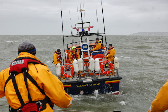 Swanage lifeboat crew coming astern towards Poole lifeboat before a crew member throws the heaving line that's attached to the tow rope during a training exercise with Poole all-weather lifeboat in Poole Bay on Sunday 23 February 2014. Photo: RNLI/Dave Riley