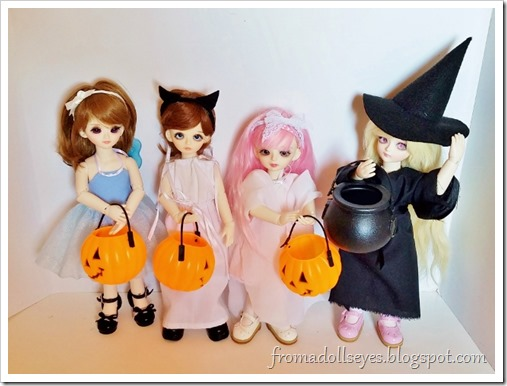 Four yosd sized ball jointed dolls all dressed in their Halloween costumes.  A fairy, a cat, a ghost, and a witch.  They are carrying cute pumpkin buckets and a plastic black cauldron for the witch costume.