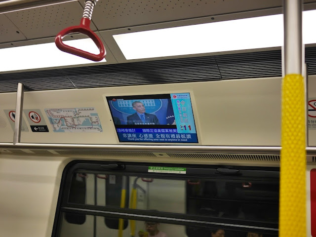 subway car video screen displaying news of a speech by Barack Obama