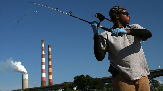A man goes fishing in the Potomac River as emissions spew out of the coal-fired Morgantown Generating Station in Newburg, Md. An effort to prevent health studies from factoring into environmental regulations has drawn howls of protest from scientists. Photo: Mark Wilson / Getty Images