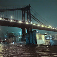 Streets are flooded under the Manhattan Bridge in the Dumbo section of Brooklyn, N.Y., Monday, Oct. 29, 2012. Sandy continued on its path Monday, as the storm forced the shutdown of mass transit, schools and financial markets, sending coastal residents fleeing, and threatening a dangerous mix of high winds and soaking rain. (AP Photo/Bebeto Matthews)