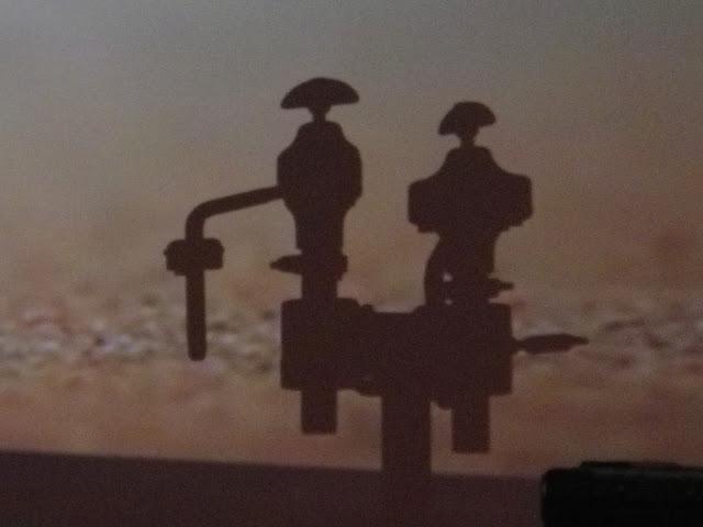 ドラムセットの部品のシルエット と 赤尾 充弥 氏の映像と のコラボ。(おそらくは偶然の産物)