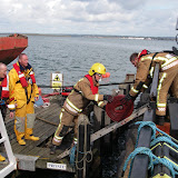 20 April 2012 - Firefighters and Poole lifeboat crews work together to unload essential equipment onto Green Island. Photo: RNLI/Poole Lifeboat Station Anne Millman