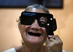 A woman laughing, looking through 'Bausch + Lomb' eye test equipment