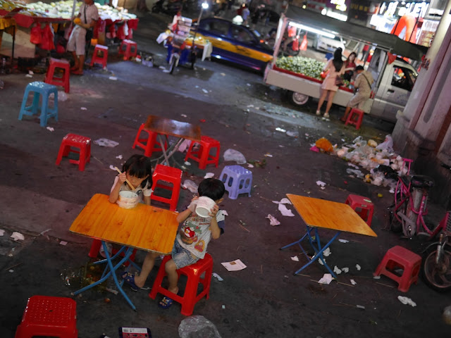 little girl and boy eating noodle soup outdoors in Zhongshan, Guangdong