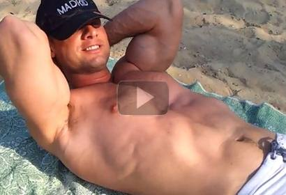 Bodybuilder Flexing Muscles on a Public Beach