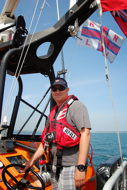 Second Coxswain Dave Riley at the helm - needing some practise in choosing fashion shorts! Photo: RNLI Poole/Oli Mallinson