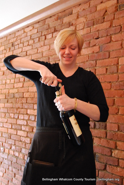 Opening a bottle of wine to be enjoyed with dinner at Flats Tapas Bar in Historic Fairhaven.Credit: Sommer Cronck