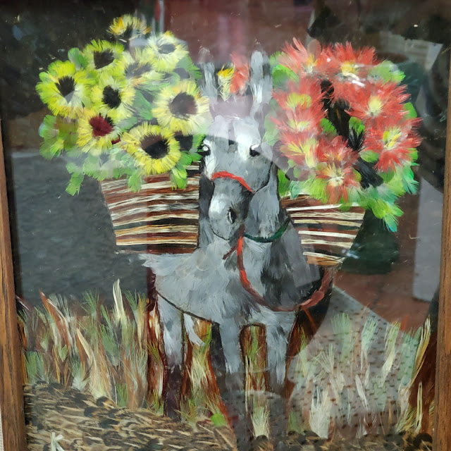 Framed artwork of a donkey carrying two baskets of sunflowers.