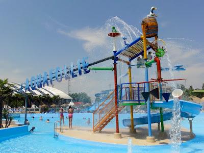"""Et stort svømmebasseng med sklier i bakgrunnen. Over bassenget er teksten """"Aquafollie""""."""