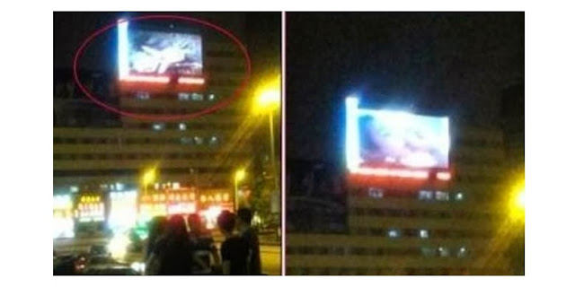 Screenshot via Sina Weibo . Video porno yang diputar di billboard digital dekat stasiun kereta Jilin City, China