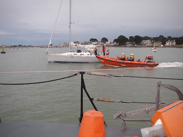 30 April 2012: Both Poole lifeboats escort a yacht back into the harbour after it issued a Mayday call when it ran aground on Hook Sands and started taking in water.  A crew member was put aboard the yacht. Photo: RNLI/Poole Lifeboat Station James Kilburn
