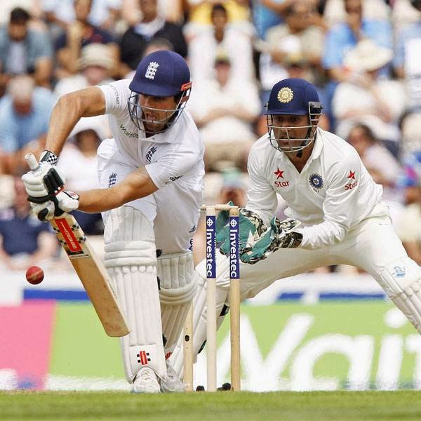England's Captain Alastair Cook (L) hits a shot watched by India's Captain and wicketkeeper MS Dhoni during the first day of the third cricket Test match between England and India at The Ageas Bowl cricket ground in Southampton on July 27, 2014.
