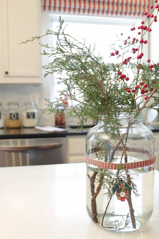 large glass container filled with pine branches and berries for Christmas
