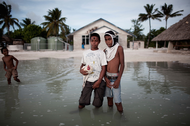 Two boys stand in sea water that has flooded their village in Kiribati. Photo: Ciril Jazbec