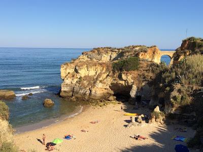 En strand med klipper og en bro i bakgrunnen.