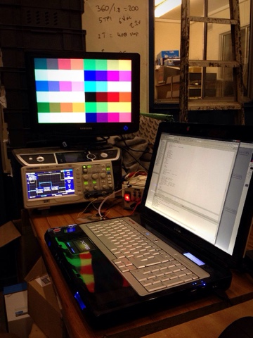 A VGA monitor displaying coloured blocks.  The monitor is on top of an oscilloscope displaying signal traces.  In the foreground a laptop is being used to edit code to run on the PIC microcontroller