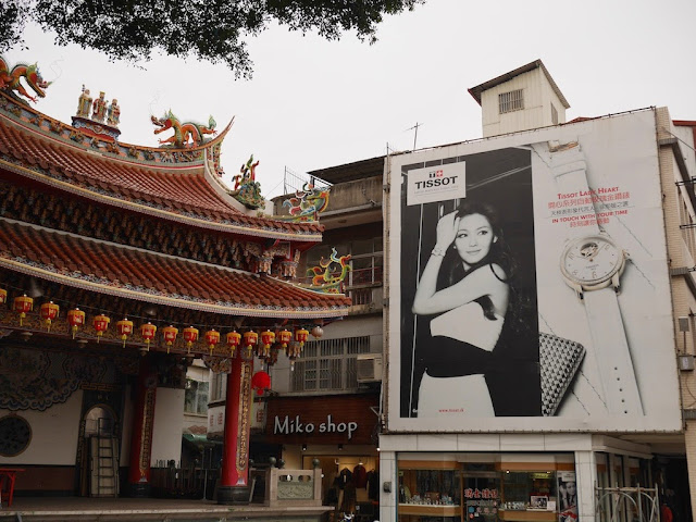Taiwanese temple stage and billboard ad for Tissot with a woman looking the other direction