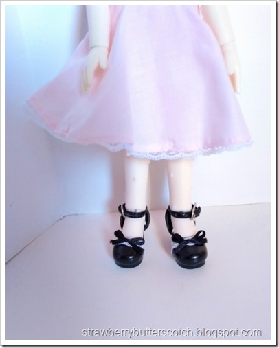 A close up of a ball jointed doll wearing her new tights made from a pair of old tights.  She is also wearing cute shoes with ankle straps and a pink dress.