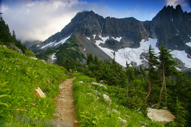 The trail crosses through green grass toward the mountainCredit: Peter James