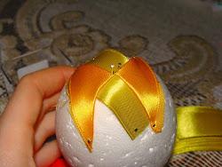 Rożki zaczynam przypinać od wierzchołka jajka, czyli tu gdzie przypięłam wcześniej wstążeczkę. Szpilkę wbijam w miejscach zgięcia wstążki, w dwóch rogach. Tu pokazuję już przypięte dwa rożki