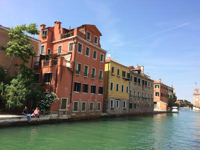 To mennesker som slapper av ved en kanal. Fargerike hus innover kanalen.