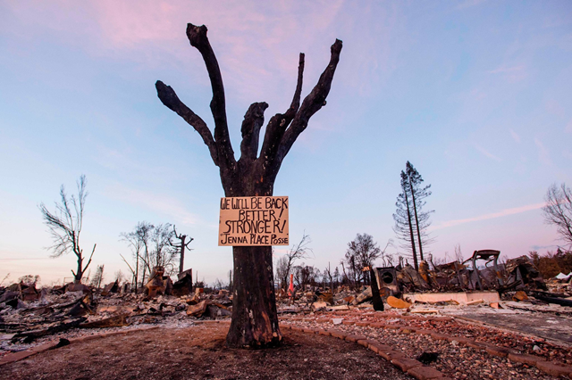 A sign of resilience hangs from a tree in a fire-destroyed neighborhood in Santa Rosa. It reads, 'We will be back. Better! Stronger! Jenna Place Posse'.  Photo: Josh Edelson / Agence France-Presse / Getty Images