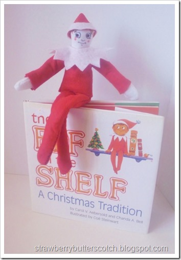 A diy elf on the shelf all dressed in felt sitting on top of a copy of the Elf on the Shelf book.