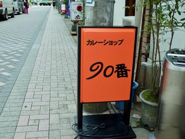カレーショップ90番と書かれた、店頭のオレンジ色の立て看板