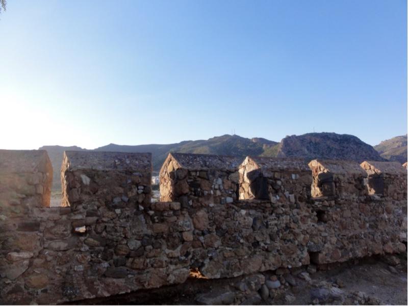Mur med brystvern, fjell i bakgrunnen.