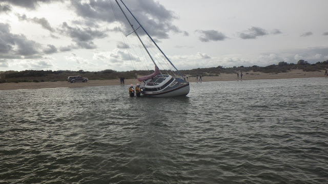 Two crew members inspect a yacht that had grounded about 30 metres offshore in Studland Bay - 5 October 2014.  Photo credit: Poole/RNLI