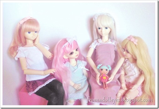 A msd sized ball jointed doll holding a lalaloopsy doll while two smaller yosd sized ball jointed dolls are looking at it and asking to play with it.  Now a second msd bjd is asking too.