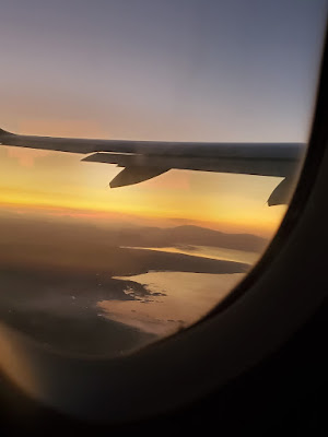 sun set view out of airplane window. land and water can be seen.