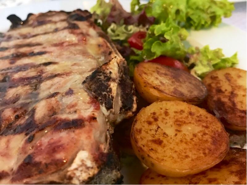 Et stort stykke kjøtt ved siden av litt poteter og salat.