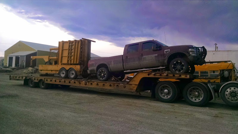 pickup truck and construction equipment loaded on flatbed trailer