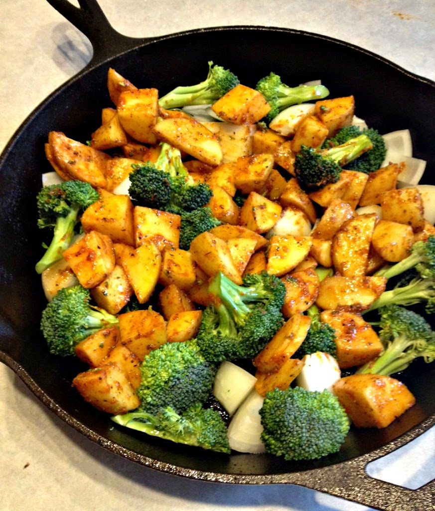 Potatoes, onions, and broccoli line the skillet and await the chicken.