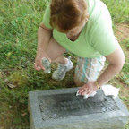 Joyce Ann Blanchard, sister of George Wilkerson cleans a tombstone with baby oil.
