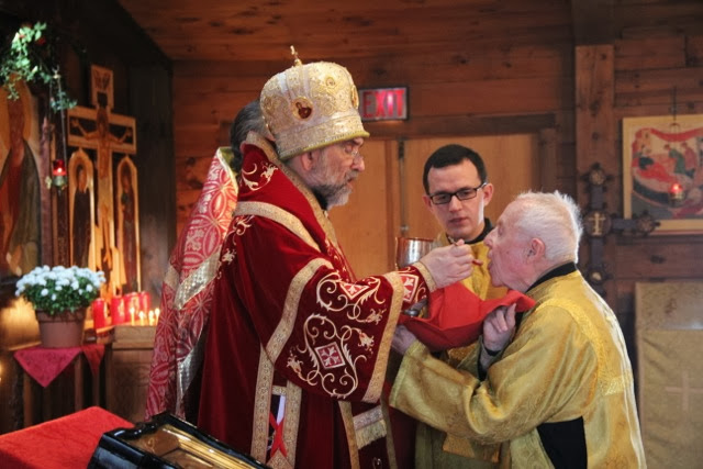 Bishop Michael communes the faithful.