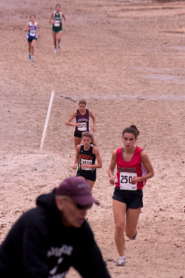 First time thru the sandpits  Ariana North leads Jossette Norris and Pagano, Catherine of Ridgewood as Jock Brown, Ridgewood coach, zooms thru the camera. Arianna was working soooo hard at this point 'The second mile I really hammered. I was just going really fast around the sand'.