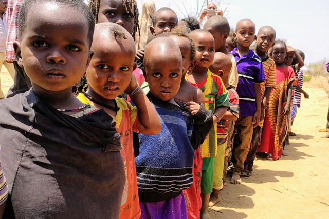 Children lining up for their one meal per day at a school in Bandarero, Northern Kenya. Photo: Daniel Pfister / OCHA