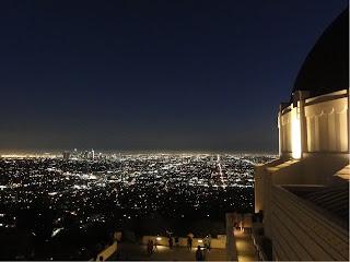 En by om kvelden med masse lys. I forgrunnen en kuppelformet bygning som også er delvis opplyst.