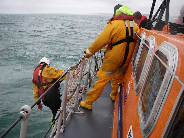 17 July 2011 – Crew Member Scott Rowland getting ready on the scramble net to retrieve a casualty from the water off Poole's all-weather lifeboat. Photo: RNLI Poole/Anne Millman