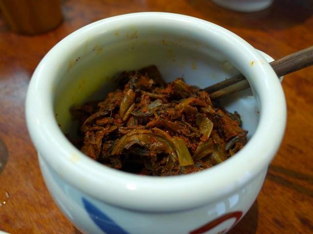 卓上の壺に入れられた激辛の辛子高菜。色がドス黒い
