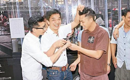 黃光亮(中)與趙永洪手執剪刀,為張建聲「落髮」。